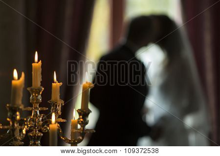 Candles And Silhouette Of The Bride And Groom At A Wedding.