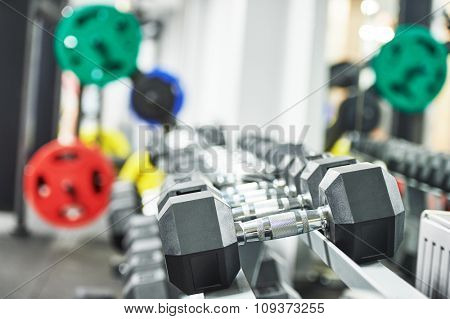 Fitness, sport and training concept. Closeup training dumbbells  in fitness gym