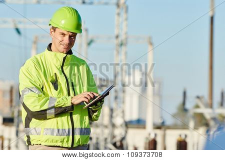 engineer builder with laptop computer at construction site near power plant