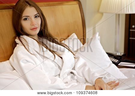 Portrait of a beautiful young adult attractive sexy and sensuality pretty brunette woman lying on the bed in bedroom