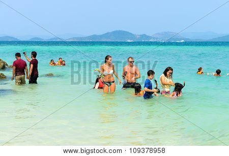 Tourists Watching The Fish And Playing Sea Water Happily On The Beach