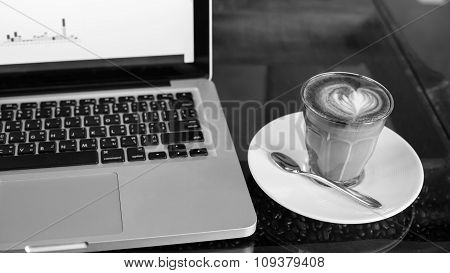 Hot Art Latte Coffee In A Cup And Laptop On Wooden Table In Coffee Shop Image.