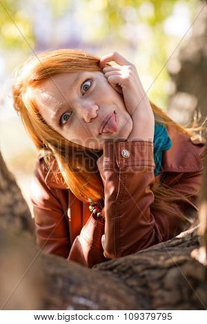 Pretty amusing redhead girl making funny face and showing tongue posing in park near tree