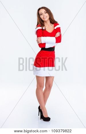 Full length portrait of a happy cute woman in santa claus cloth standing with arms folded isolated on a white background