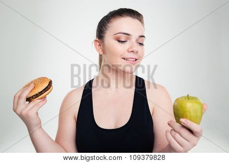 Portrait of a happy fat woman choosing between burger or apple isolated on a white background