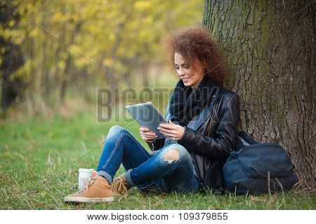 Portrait of a happy attractive woman with curly hair using tablet computer under tree outdoors