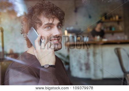 Curly attractive young smiling man sitting in cafe and talking on mobile phone