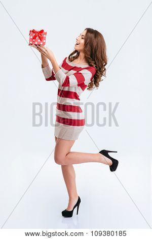 Full length portrait of a happy cute woman in dress holding gift box isolated on a white background