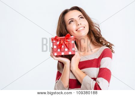 Portrait of a happy thoughtful woman holding gift box and looking up isolated on a white background