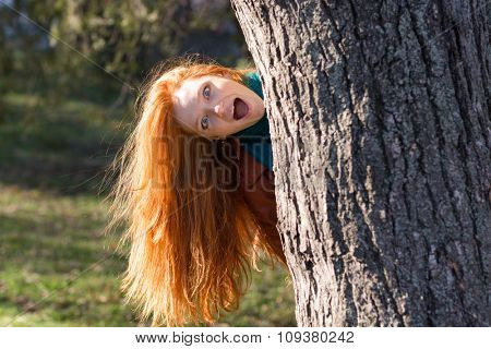 Amusing funny girl with beautiful long red hair looking out from the tree in park