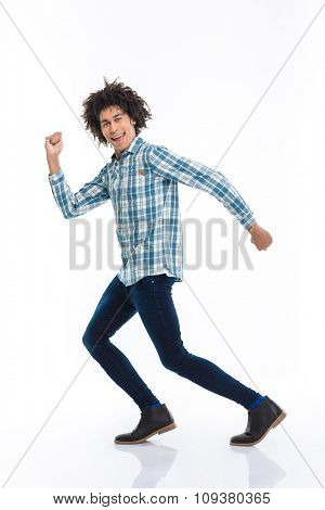 Full length portrait of a smiling afro american man running isolated on a white background