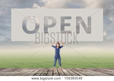 Open, words on blank board hold by a young girl in the outdoor.