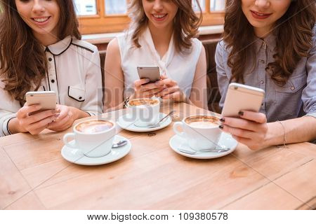 Closeup portrait of a three women using smartphones in cafe