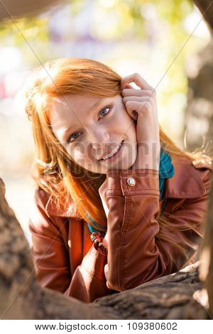 Positive cheerful cute young woman with red hair in leather jacket posing near the tree in the park