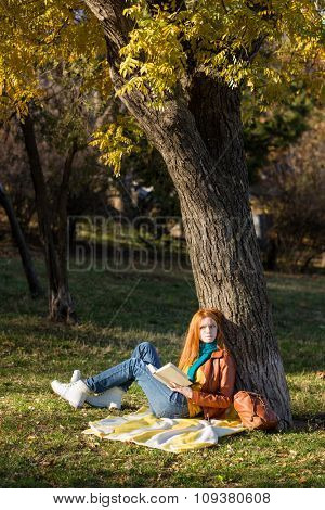 Thoughtful young redhead woman reading a book sitting under the tree in park and dreaming