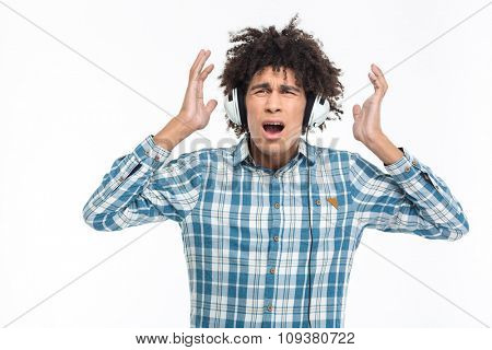 Portrait of a shocked afro american man in headphoes listening music isolated on a white background