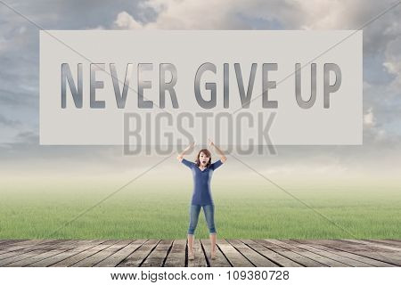 Never give up, words on blank board hold by a young girl in the outdoor.