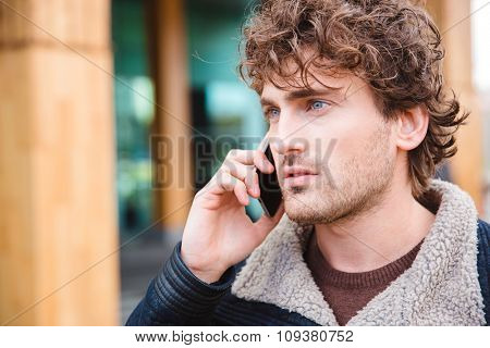Closeup of handsome attractive serious concentrated curly young male talking on cellphone