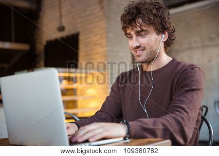 Concentrated smiling happy pleased content curly male in brown sweetshirt using laptop and listening to music