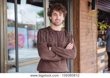 Portrait of positive happy cheerful curly young man in brown sweetshirt standing with crossed arms