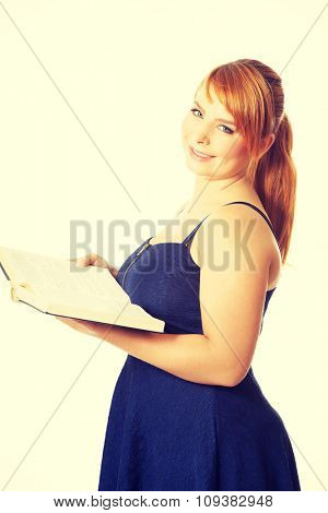 Overweight woman in skirt holding a book