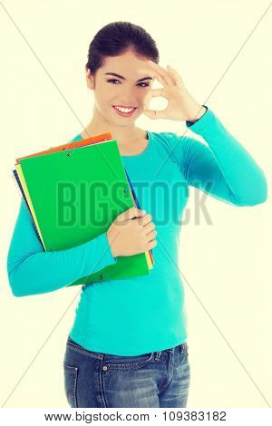 Young woman making ok sign holding notes.