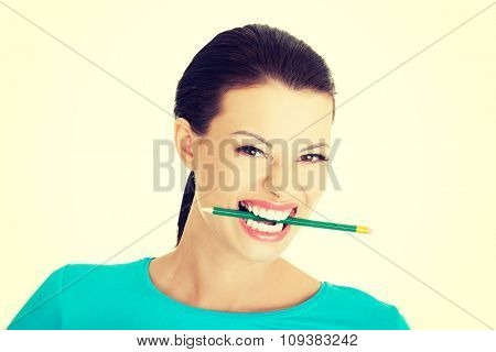 Portrait of a woman biting her pencil.