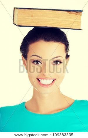 Portrait of a woman holding book on her head.