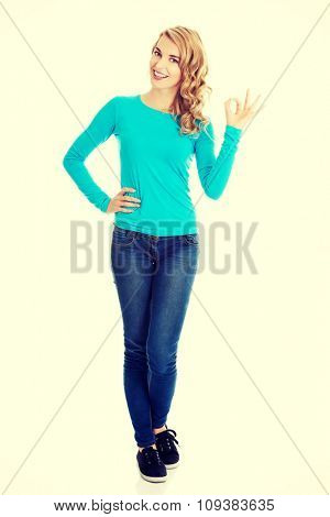 Full length woman showing ok sign.