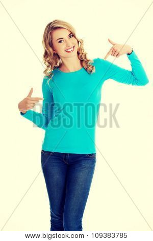 Smiling woman pointing at her shirt.