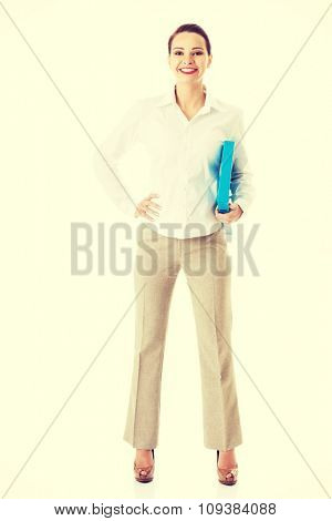 Full length businesswoman holding binder.