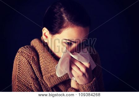 Portrait of a woman sneezing to tissue