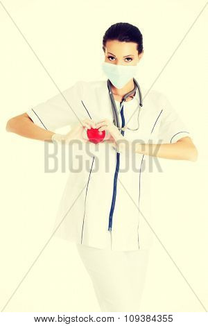 Female doctor in protecting mask holding heart model.