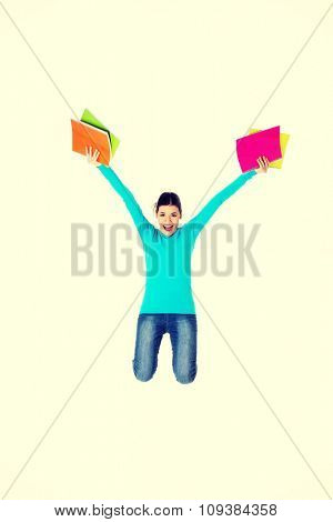 Full length woman jumping with notebooks.