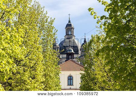Baroque Monastery Through Green Trees