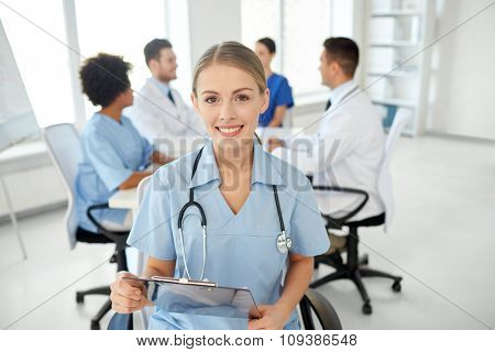 health care, profession, people and medicine concept - happy female doctor or nurse with clipboard over group of medics meeting at hospital