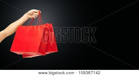 people, sale, consumerism, advertisement and black friday concept - close up of hand holding red blank shopping bags