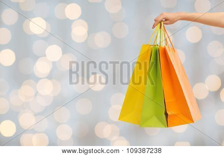 people, sale, consumerism and advertisement concept - close up of hand holding shopping bags over holidays lights background