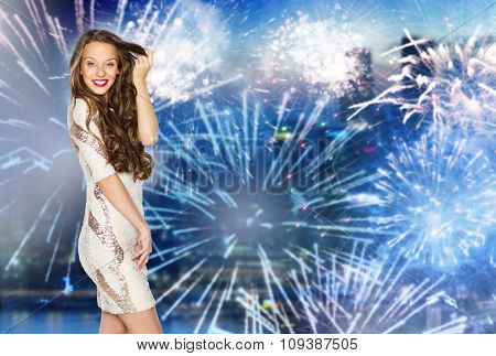 people, style, holidays, hairstyle and fashion concept - happy young woman or teen girl in fancy dress with sequins touching long wavy hair over firework at night city background