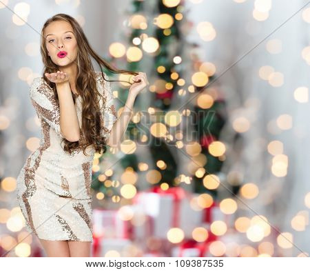 people, holidays, hairstyle and fashion concept - happy young woman or teen girl in fancy dress with sequins and long wavy hair sending blow kiss over christmas tree lights background