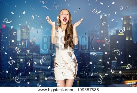 people, holidays, emotion and glamour concept - happy young woman or teen girl in fancy dress with sequins and confetti at party over night singapore city background
