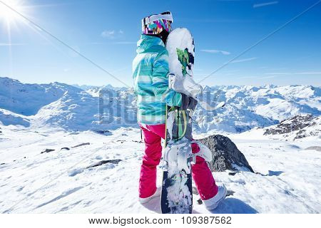 Back view of female snowboarder wearing colorful helmet, blue jacket, grey gloves and pink pants standing with snowboard in hand and enjoying sunny alpine mountain landscape - winter sports concept
