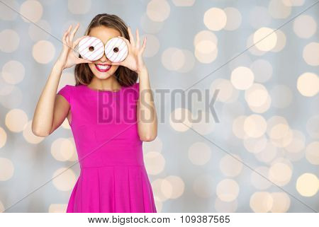 people, holidays, junk food and fast food concept - happy young woman or teen girl in pink dress having fun and looking through donuts over lights background