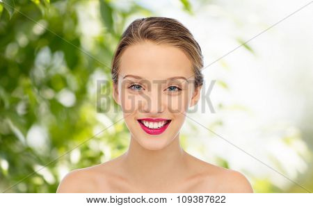 beauty, people and health concept - smiling young woman face with pink lipstick on lips and shoulders over green natural background