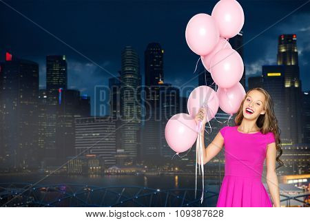 people, holidays, party, nightlife and fashion concept - happy young woman or teen girl in pink dress with helium air balloons over night singapore city background