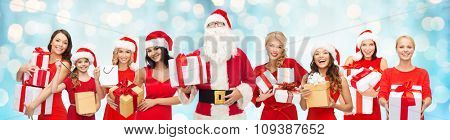 people, holidays, christmas and celebration concept - santa calaus and happy women with gift boxes over blue holidays lights background