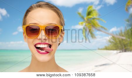 people, expression, summer vacation, travel and fashion concept - smiling young woman in sunglasses with pink lipstick on lips showing tongue over tropical beach with palm background