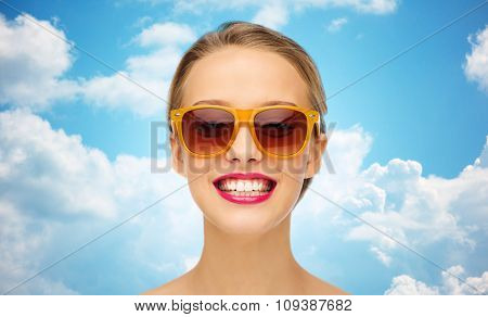beauty, people, accessory and fashion concept - smiling young woman in sunglasses with pink lipstick on lips over blue sky and clouds background