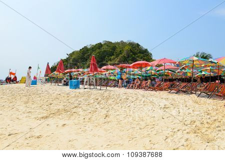 People Relaxing, Beach Chairs And Colorful Umbrella On The Beach