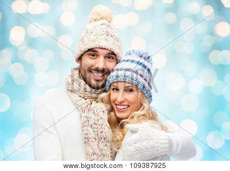 winter, fashion, couple, christmas and people concept - smiling man and woman in hats and scarf hugging over blue holidays lights background